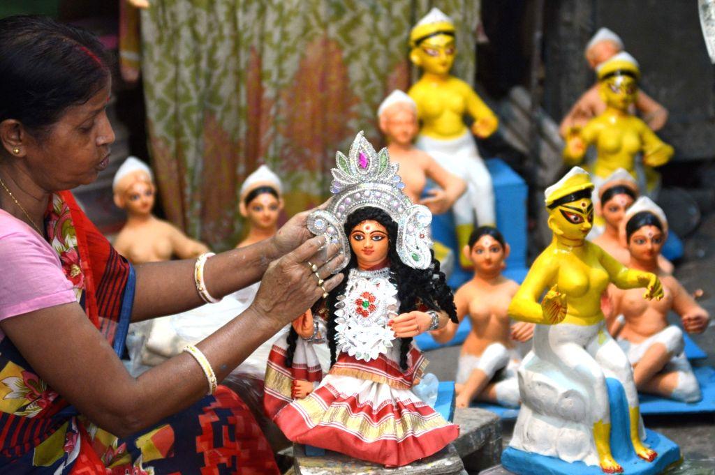 An artiste decorates an idol of Goddess Laxmi ahead of Laxmi Puja celebrations, at a Kumartoli workshop in Kolkata on Oct 10, 2019.