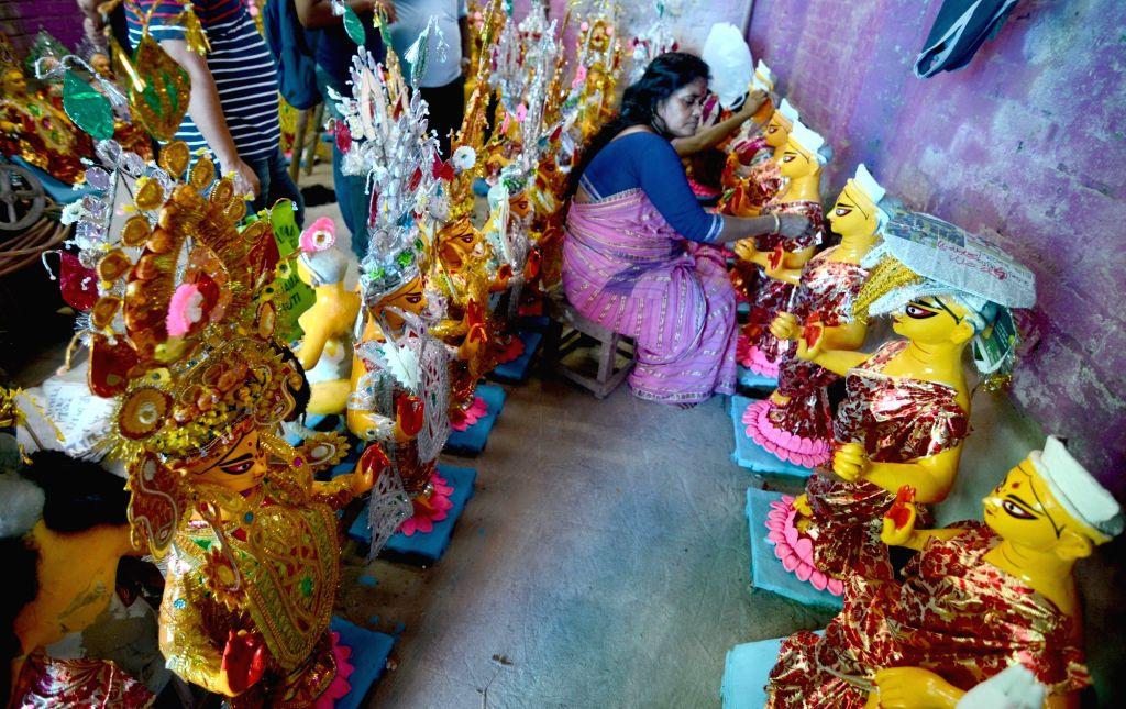 An artiste gives finishing touches to an idol of Goddess Laxmi ahead of Laxmi Puja celebrations, at a Kumartoli workshop in Kolkata on Oct 10, 2019.