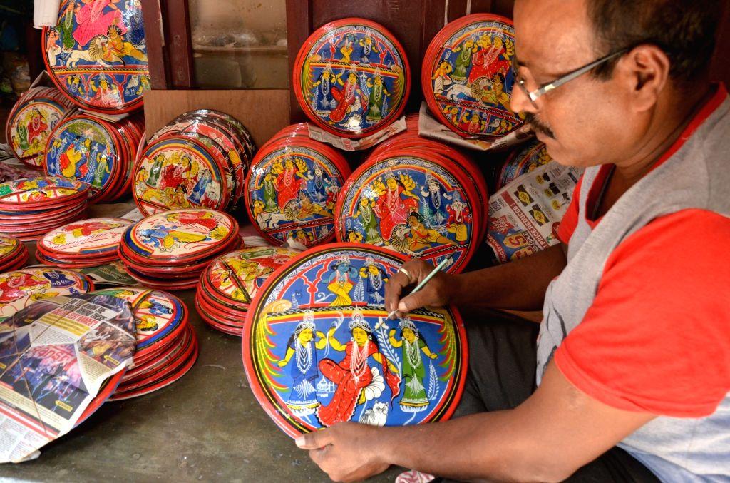 An artiste paints an image of Goddess Laxmi on a showpiece ahead of Laxmi Puja celebrations, at a Kumartoli workshop in Kolkata on Oct 10, 2019.