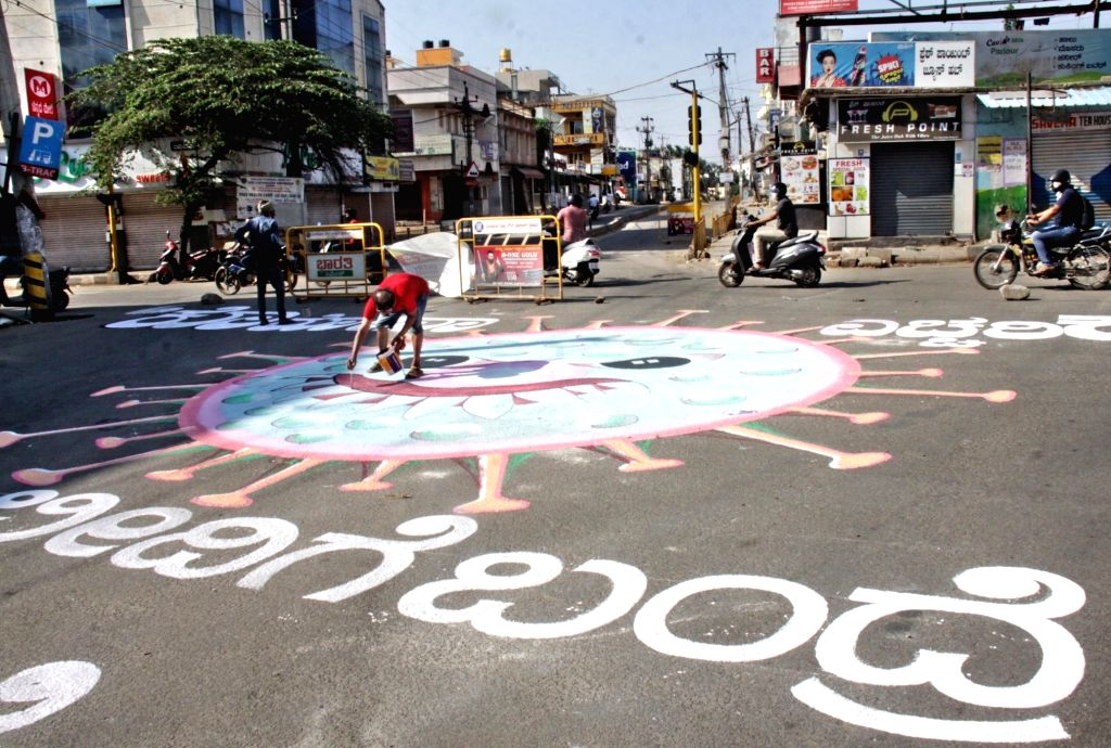 An artiste paints the image of Coronavirus at a road adjoining MS Palya Junction to spread awareness among people about the disease, during the 21-day nationwide lockdown imposed as a ...