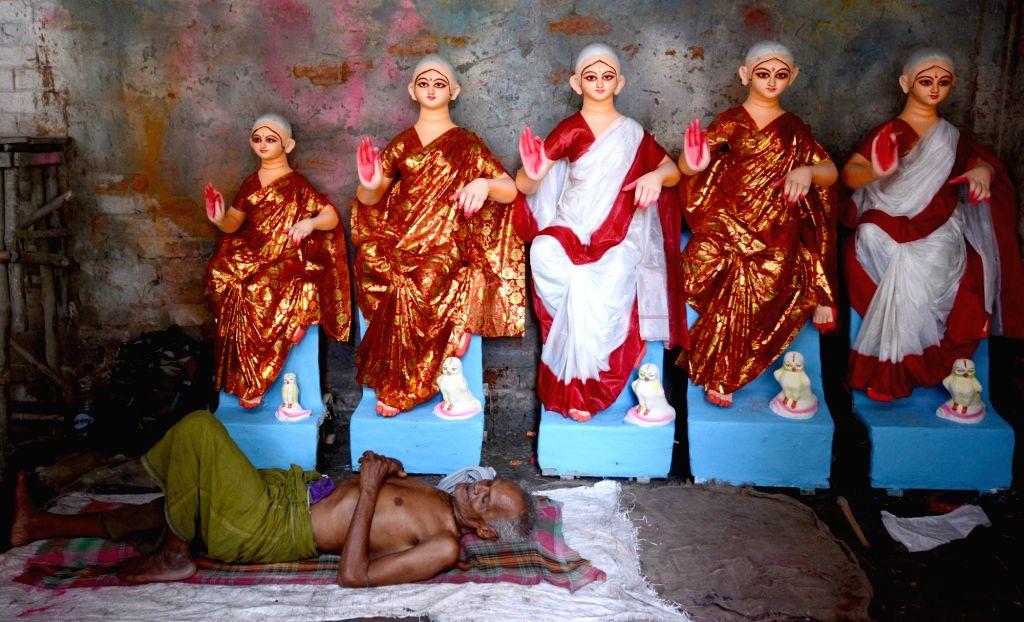 An artiste takes a nap with unfinished idols of Goddess Laxmi besides him, at a Kumartoli workshop in Kolkata on Oct 10, 2019.