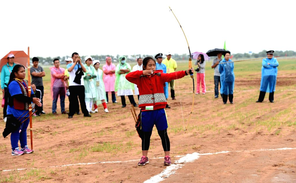 An athlete from southeast China's Taiwan perform Taiwanese archery during the 10th National Traditional Games of Ethnic Minorities of China in Ordos, north China's ...