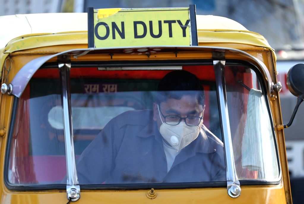 An auto-rickshaw driver wears a mask as a precautionary measure against COVID-19 (coronavirus), at Delhi's Connaught Place on March 18, 2020.