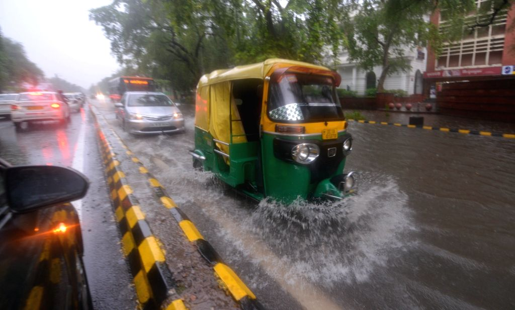 An auto-rickshaw struggles through a water logged road in Connaught Place of New Delhi on July 13, 2018.
