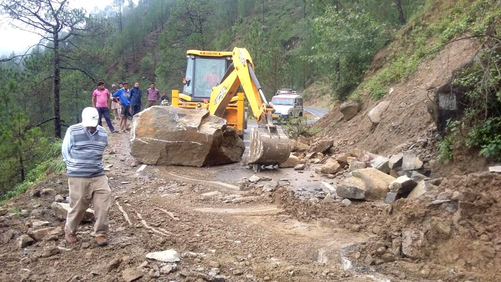 An earth-mover pressed into service to repair roads destroyed due to landslides in Chamoli of Uttarakhand on July 3, 2016.