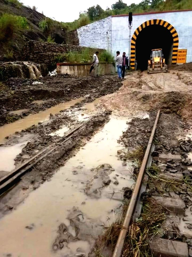 An earth-mover removes mud from railway tracks in Assam on June 14, 2018. Running of trains has been affected in the Lumding-Badarpur hill section of Assam following landslides triggered by ...