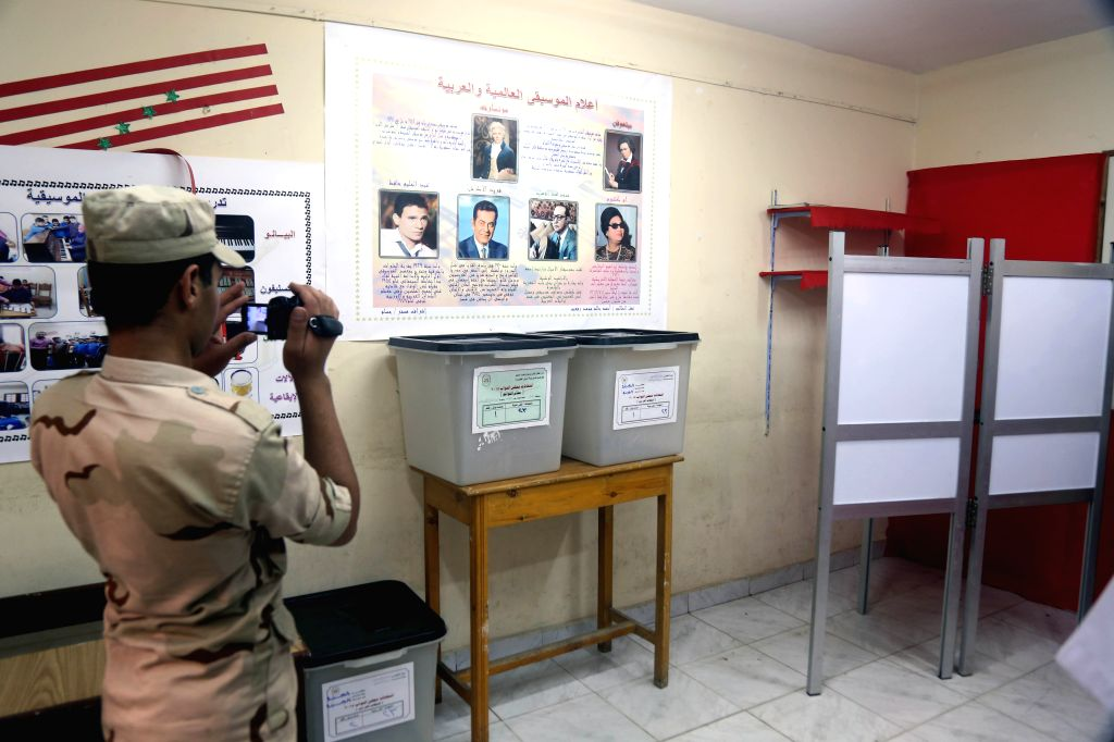 An Egyptian soldier takes video inside a polling station in Giza, Egypt, Oct. 17, 2015. The first phase of Egypt's parliamentary election covering 14 out of its 27 ...