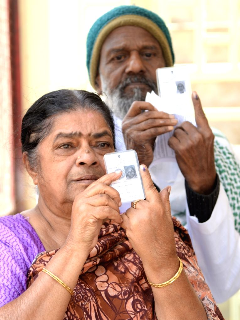 An elderly couple shows their inked finger after casting their vote for Karnataka bye-polls in Bengaluru on Dec 5, 2019.