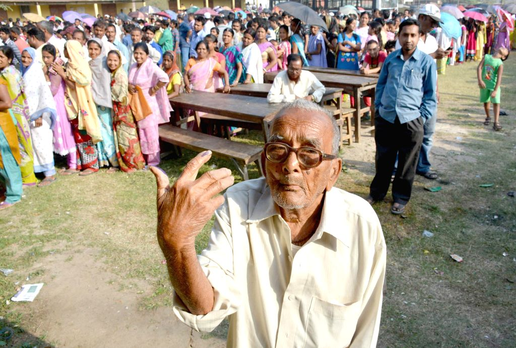 An elderly gentleman shows his fore finger marked with phosphorous ink after casting his vote at a polling booth during the sixth phase of 2014 Lok Sabha Polls in Guwahati on April 24, 2014.