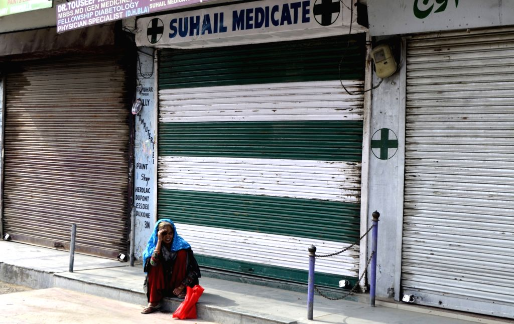 An elderly lady sits outside a chemist's shop during a shut down in Baramulla of Jammu and Kashmir on July 18, 2019.