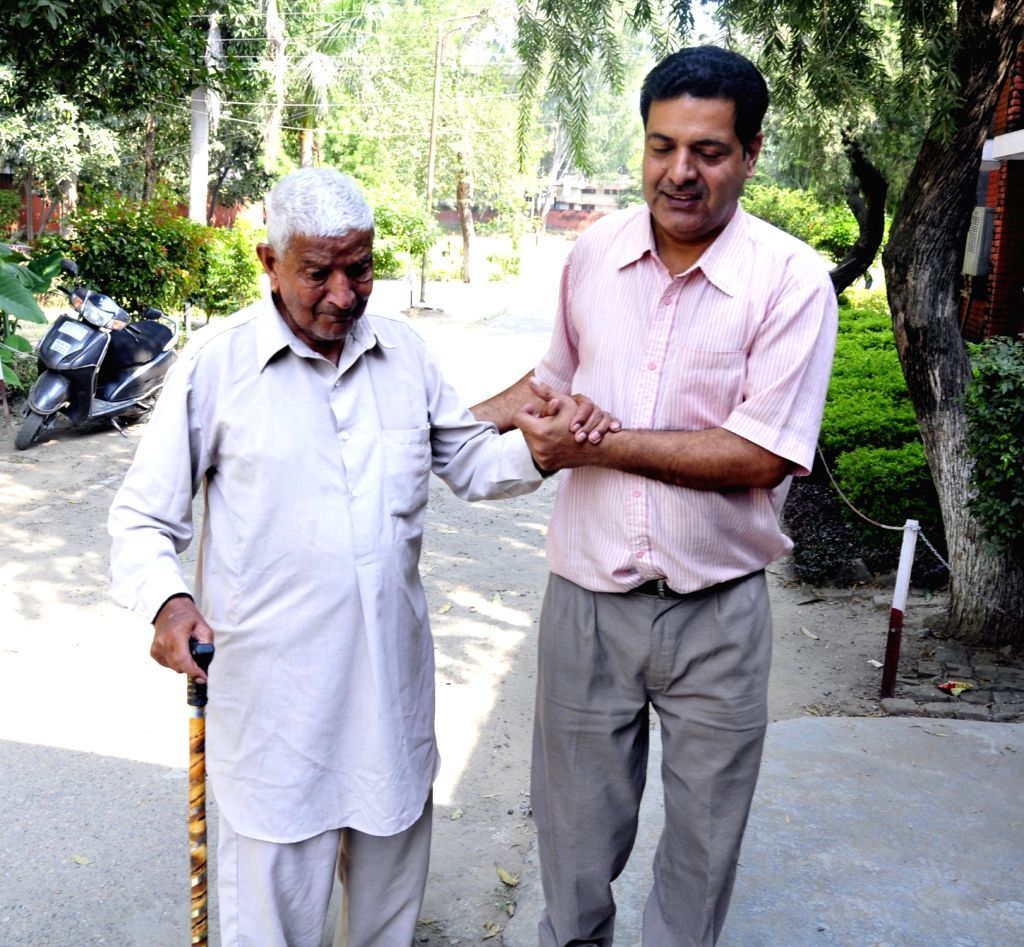 An elderly man being escorted to a polling booth during Gurdaspur Lok Sabha bypoll in Pathankot, Punjab on Oct 11, 2017.
