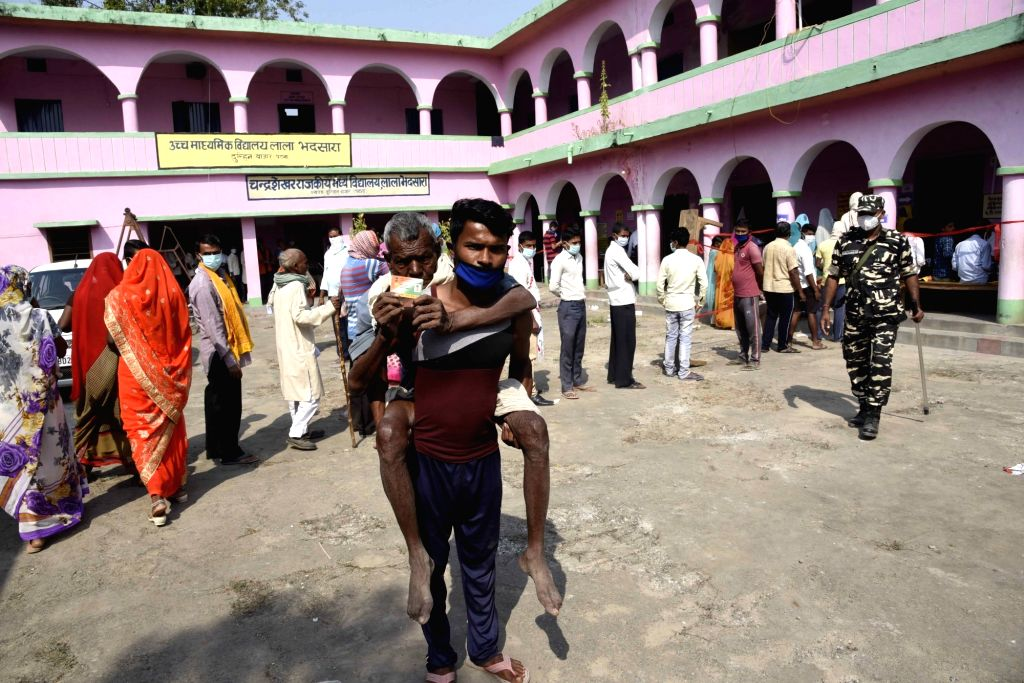 An elderly voter being assisted by a family member to a polling booth as he arrives to cast his vote for the first phase of Bihar Assembly elections, at Paliganj in Patna district on Oct 28, ...