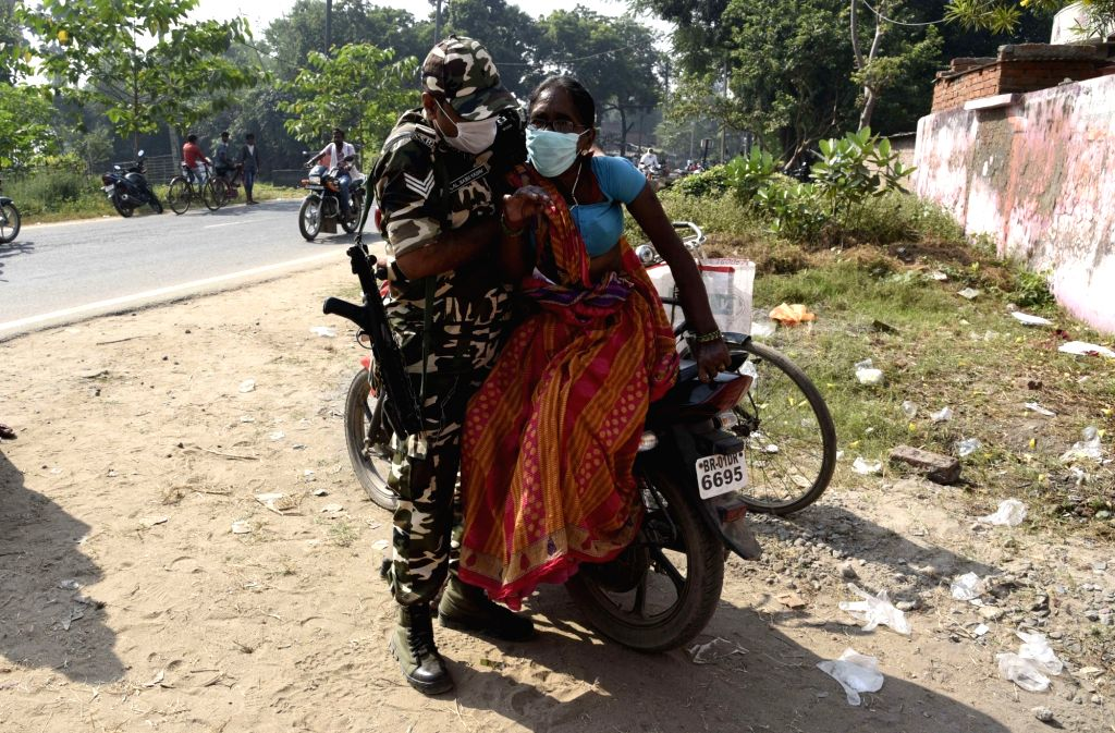 An elderly voter being assisted by a security personnel to a polling booth as she arrives to cast her vote for the first phase of Bihar Assembly elections, at Paliganj in Patna district on Oct ...