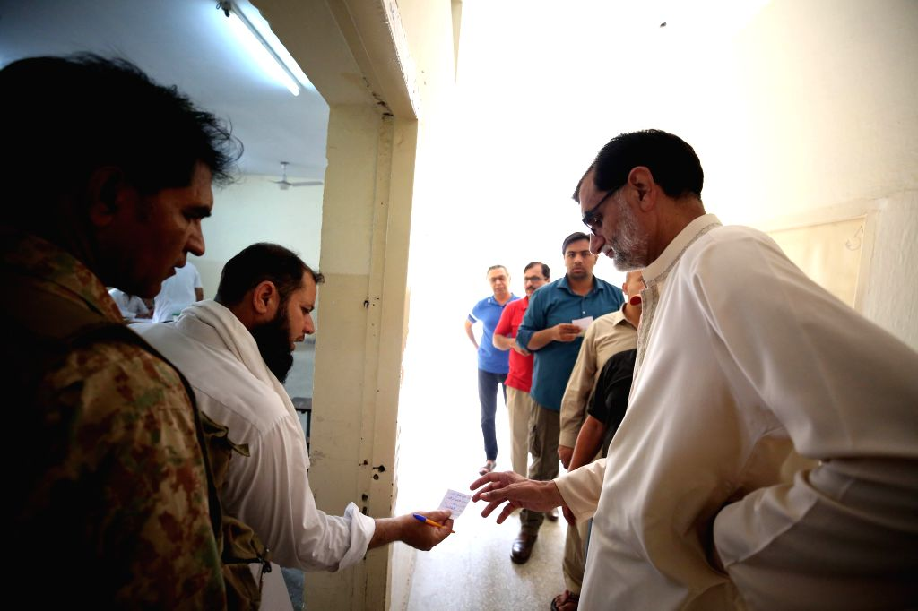 :An election official checks data of voters outside a polling station in Islamabad, capital of Pakistan, on July 25, 2018. Pakistanis started casting votes in ...