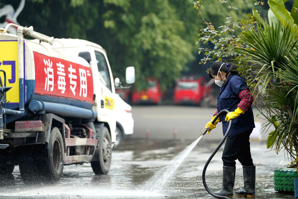An employee disinfects the ground at Chongqing Mexin Group in southwest China's Chongqing Municipality, Feb. 12, 2020. The municipality government is cooperating ...