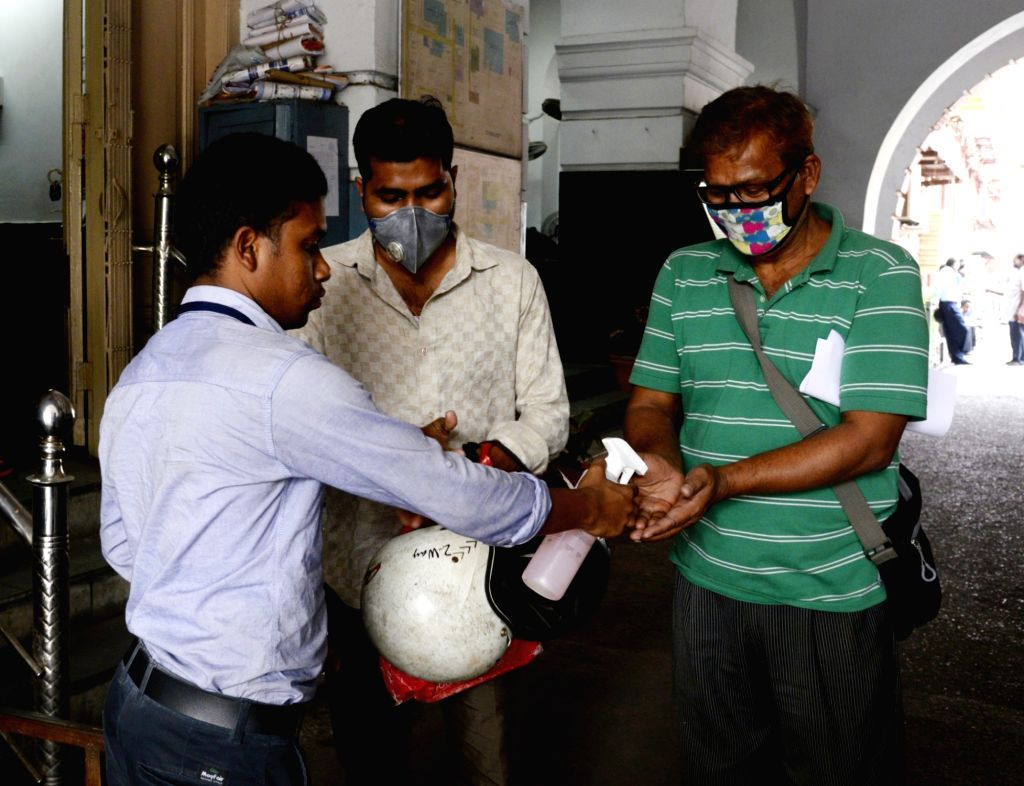An employee of the Kolkata Municipal Corporation (KMC) being given hand sanitiser as a precautionary measure to contain the spread of COVID-19 (coronavirus), on March 18, 2020.