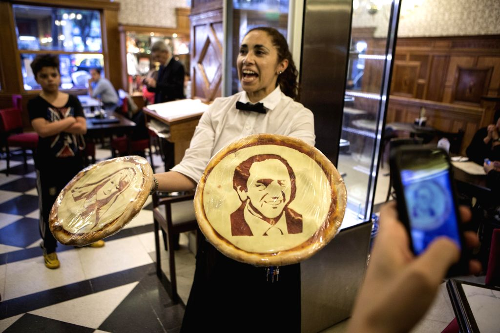 """An employee shows pizzas with the faces of presidential candidates Daniel Scioli (R) and Margarita Stolbizer (L) at the """"Los 36 Billares"""" pizza ..."""