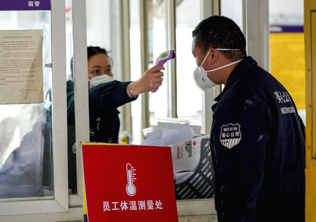 An employee takes temperature checking at a staff domitory of Chongqing Mexin Group in southwest China's Chongqing Municipality, Feb. 12, 2020. The municipality ...