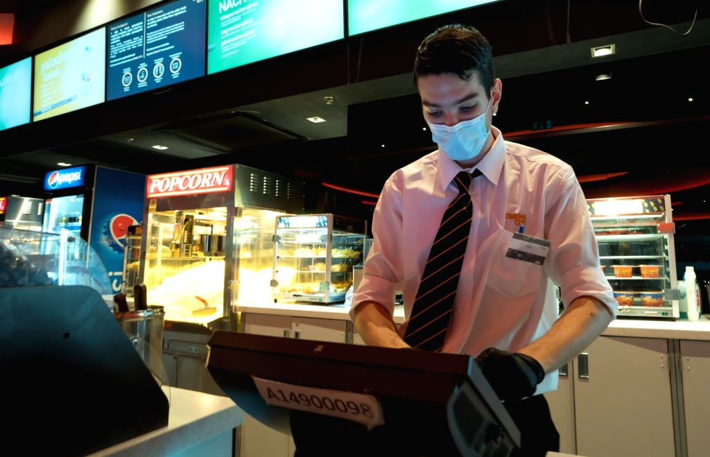 An employee wearing a face mask and gloves works at a Cinema City movie theatre in Budapest, Hungary, July 2, 2020.