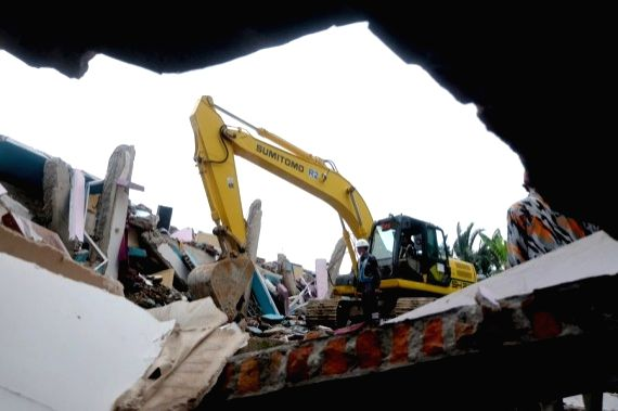 An excavator works on damaged buildings during a search operation after a 6.2-magnitude earthquake in Mamuju, West Sulawesi, Indonesia, Jan. 17, 2021.