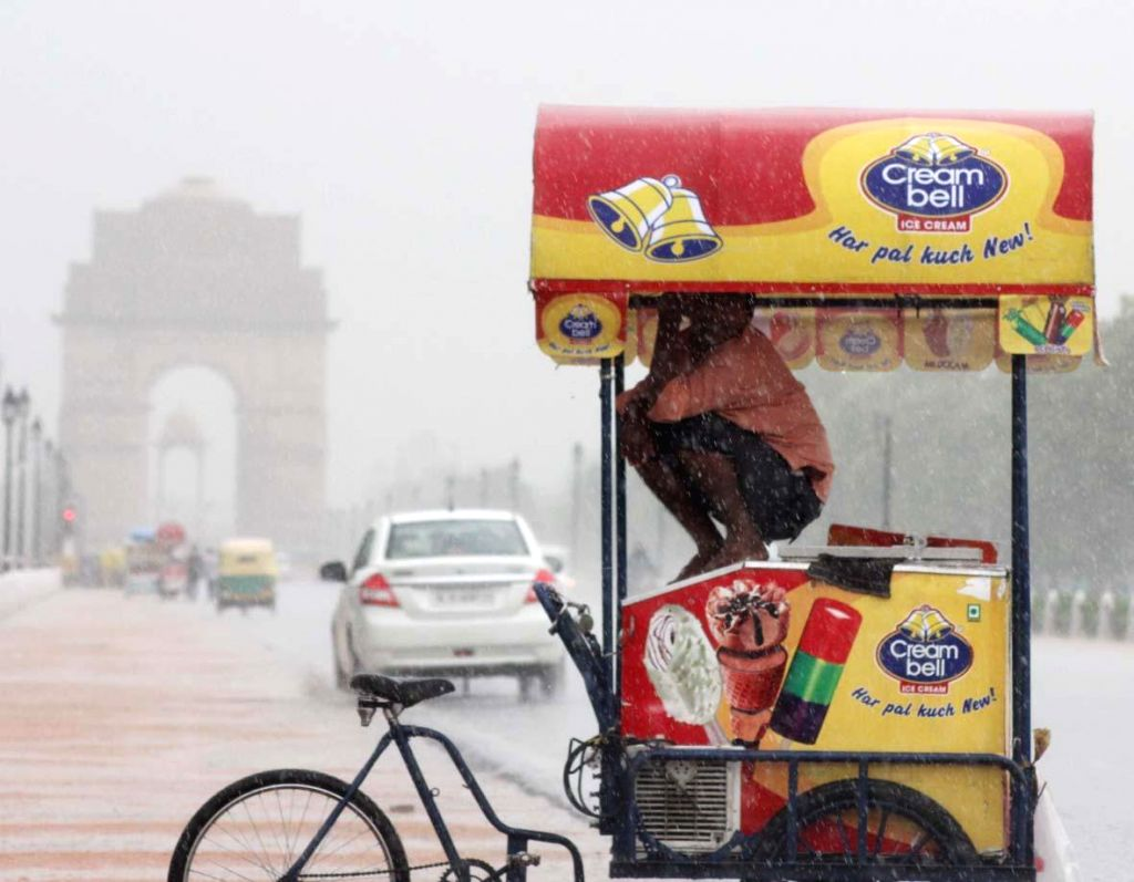 An ice-cream vendor sits on his van to shield himself from rains at India Gate in New Delhi on July 2, 2014.