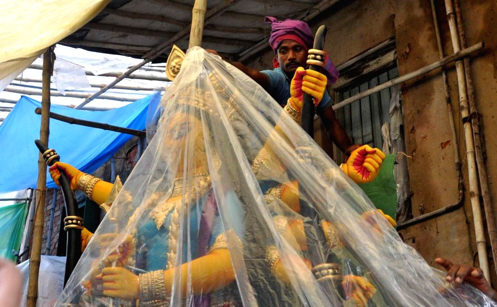 An idol of Goddess Durga being covered with plastic sheet at a workshop ahead of its transportation to a community puja pandal for Durga Puja celebrations, in Kolkata on Sep 27, 2019.