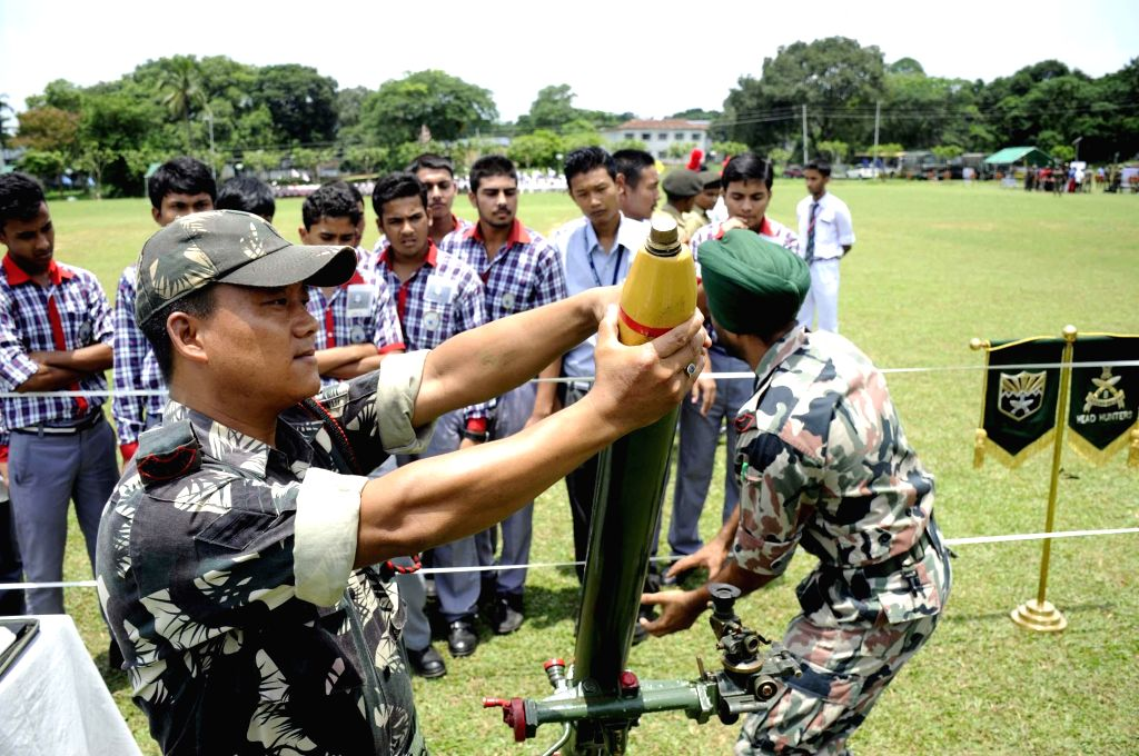 An Indian army personnel demonstrates how to operate mortars to school students during  `Know Your Army`- a programme organised by Indian Army at Assam Rifles ground in Agartala on July 9, 2014.