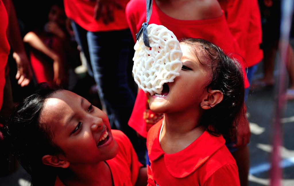 An Indonesian girl competes in a game at a celebration marking Indonesia's 70th Independence Day in Jakarta, Indonesia, Aug. 17, 2015.