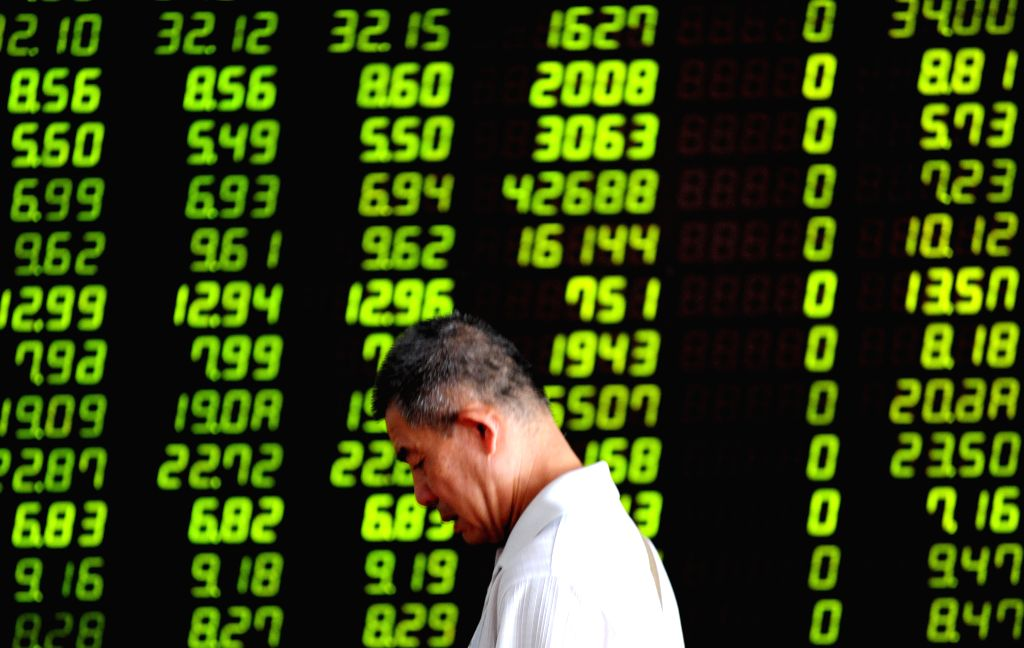 An investor walks past a stock screen in Shenyang, capital of northeast China's Liaoning Province, July 30, 2015. Chinese shares extended slumps on Thursday, with ...