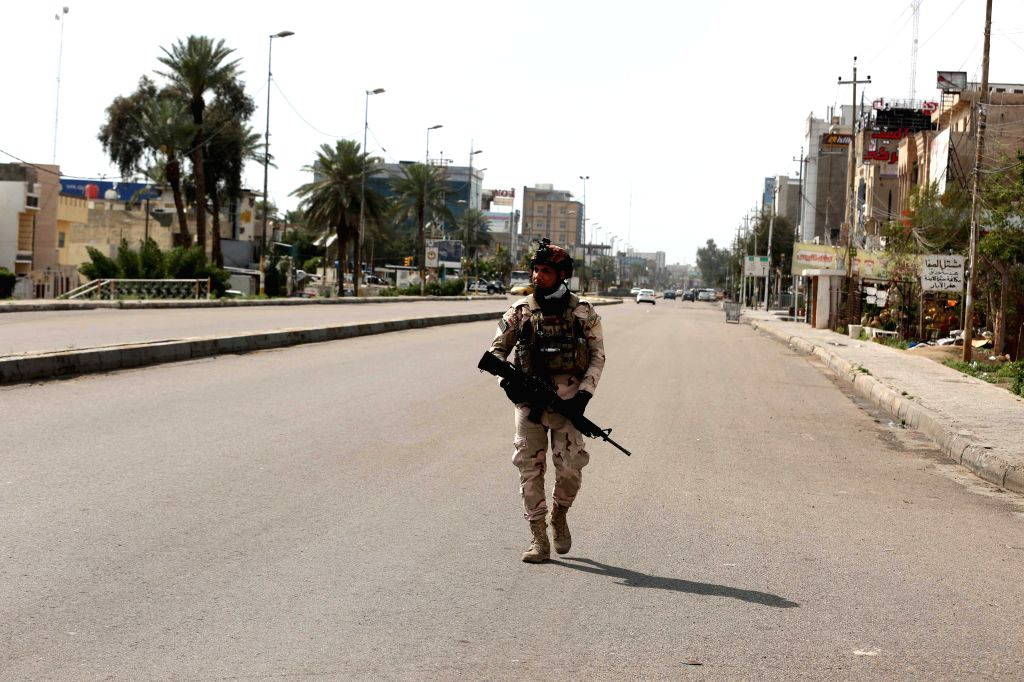 An Iraqi security member is seen on an empty street in Baghdad, Iraq on March 18, 2020. As one of the precautionary measures against the outbreak of COVID-19, the ...