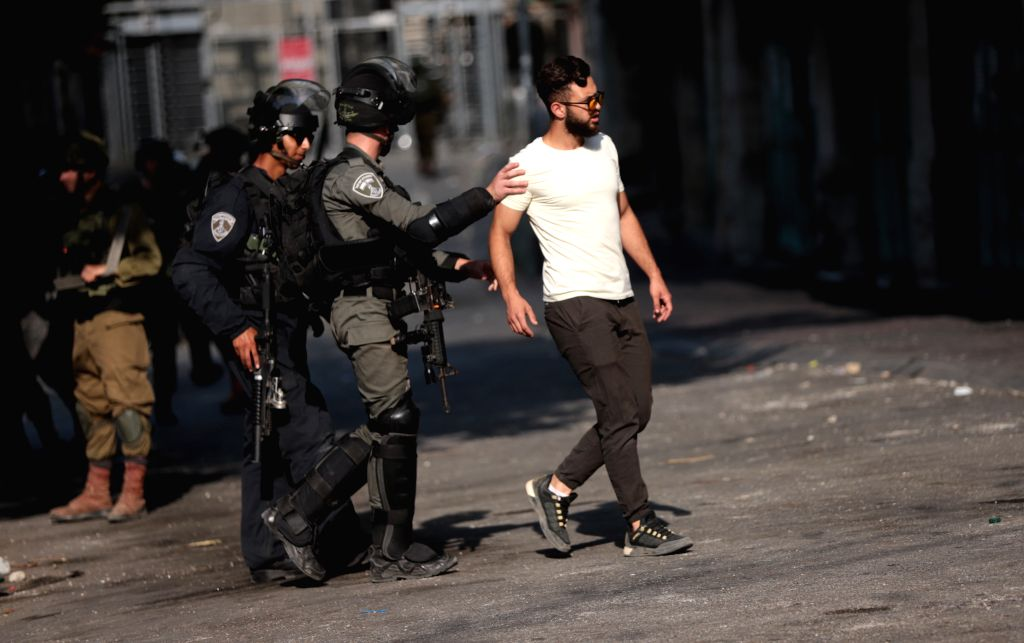 An Israeli border police member detains a Palestinian protester during clashes following a protest against the Israeli annexation plan, in the West Bank city of ...