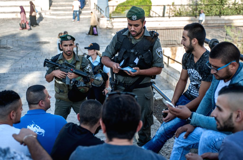 An Israeli border policeman checks Palestinians' IDs at Damascus Gate in the Old City of Jerusalem, on Oct. 16, 2015. Five Palestinians were killed on Friday in ...