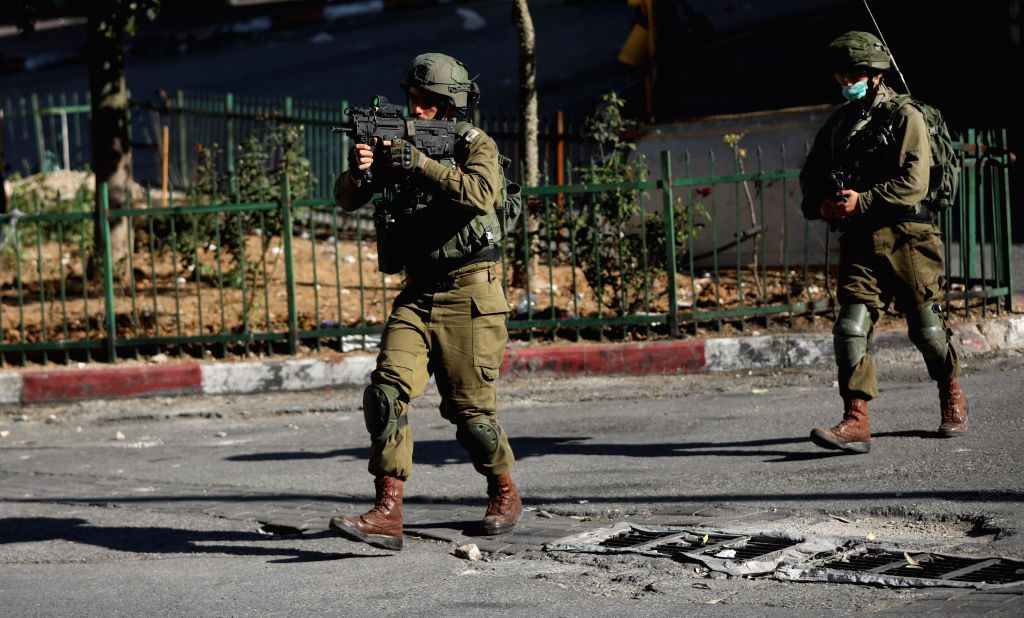 An Israeli soldier aims his weapon at Palestinian protesters during clashes after a protest against the Israeli annexation plan in the West Bank city of Hebron, on ...