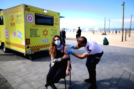 An Israeli woman gets vaccinated against the COVID-19 at a temporary facility set up by the Israeli Magen David Adom national emergency service in Tel Aviv, Israel, on Feb. 20, 2021.