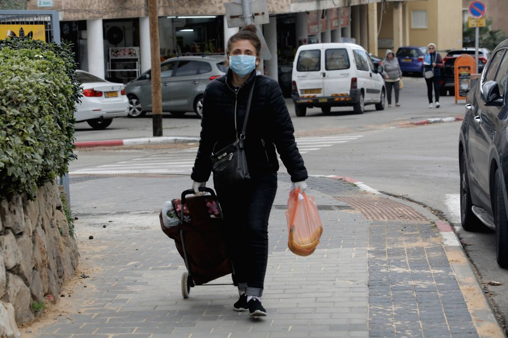 An Israeli woman wearing mask is seen in the Israeli city of Bat Yam near Tel Aviv on March 18, 2020. A total of 90 Israelis tested positive for COVID-19 on ...