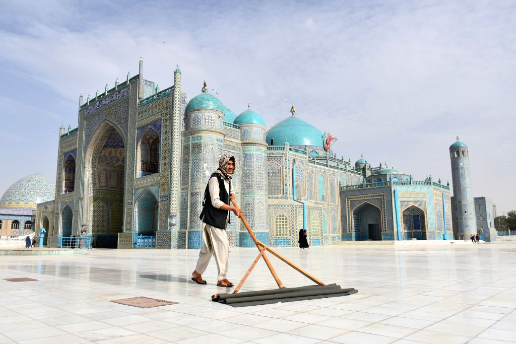 An man cleans the yard of the Blue Mosque in Mazar-i-Sharif, capital of Balkh province, northern Afghanistan, July 12, 2020. After a five-month shutdown due to the ...