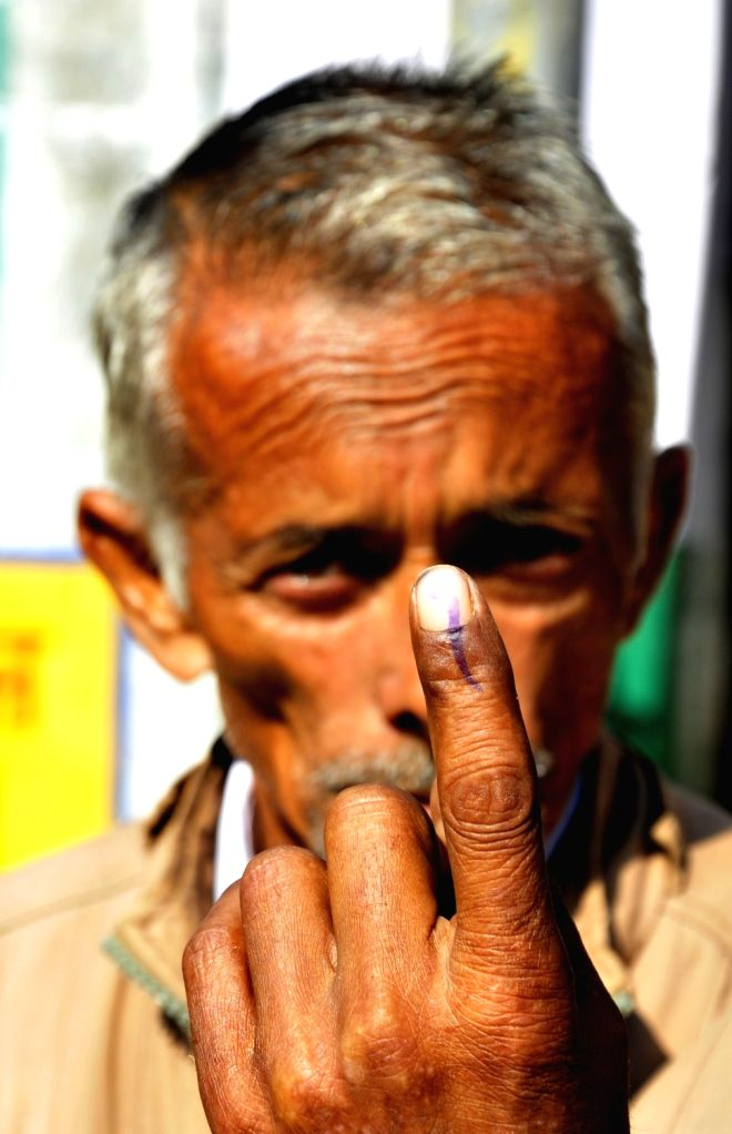 An man shows his inked finger after casting vote for Gurdaspur Lok Sabha bypoll in Pathankot, Punjab on Oct 11, 2017.