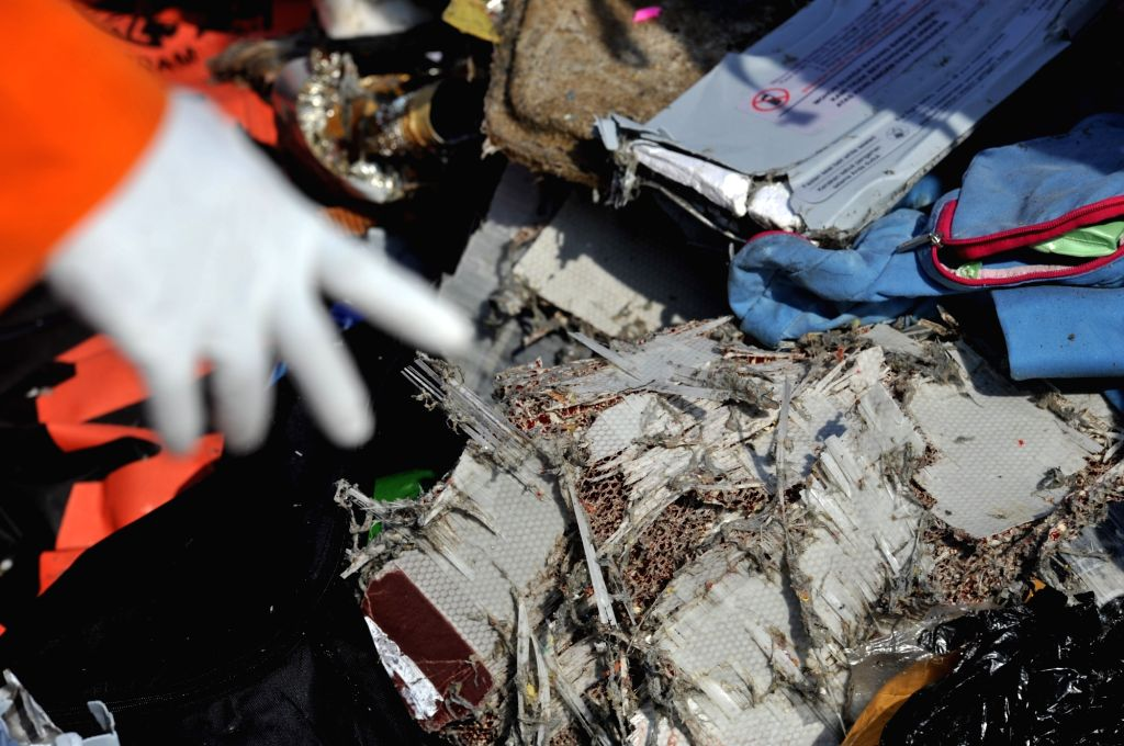 : An officer of the Search and Rescue shows the debris of the Lion Air plane found on the sea, at the Tanjung Priok port, Jakarta, Indonesia, Oct. 29, 2018. A ...