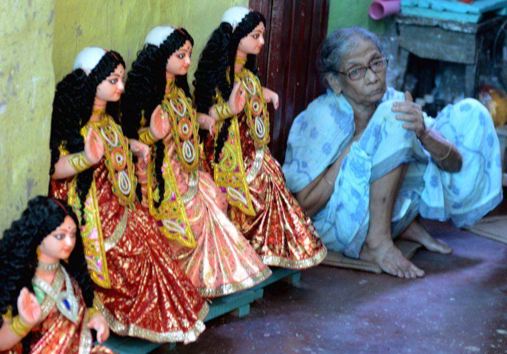 An old lady sits besides idols of Goddess Laxmi, at a Kumartoli workshop in Kolkata on Oct 10, 2019.