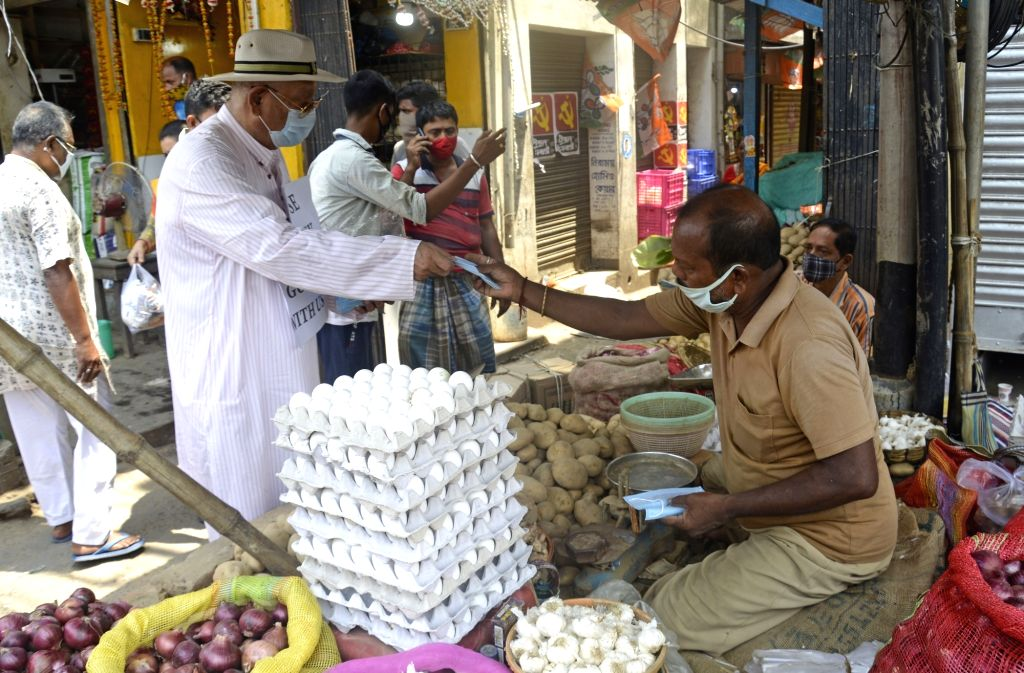 An old man distributed masks and sanitizers to people during the increasing numbers of COVID 19 patients in Kolkata .