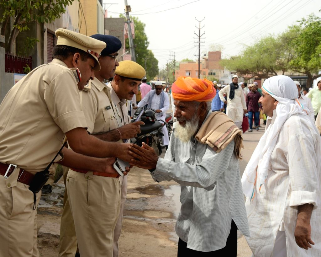 An old man greets policemen on Eid-al-Fitr in Bikaner on July 7, 2016.