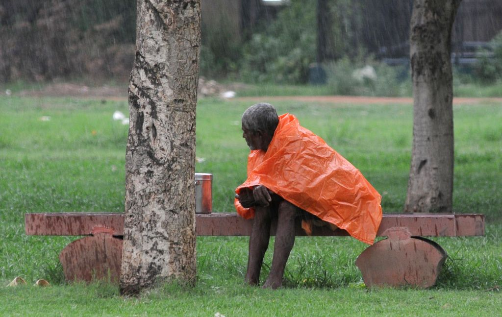 An old man uses a plastic sheet to shield himself from rains in a New Delhi park on July 6, 2014.