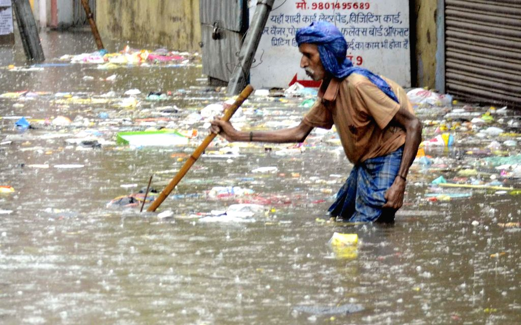An old man wades through a waterlogged street of Patna on Aug 14, 2014.