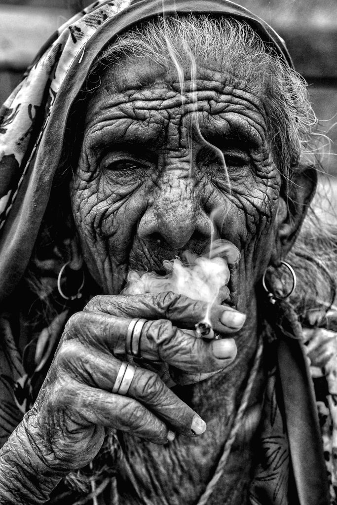 An old woman smoking, in Ajmer on June 13, 2019.