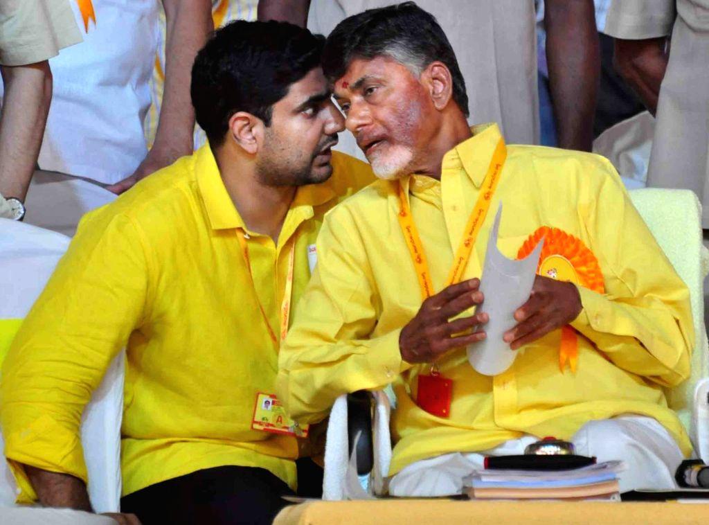 Andhra Pradesh Chief Minister and TDP chief N Chandrababu Naidu interacts with son Nara Lokesh during Telugu Desam Party's 'Mahanadu' -mega-convention- in Tirupathi on May 28, 2016. - N Chandrababu Naidu