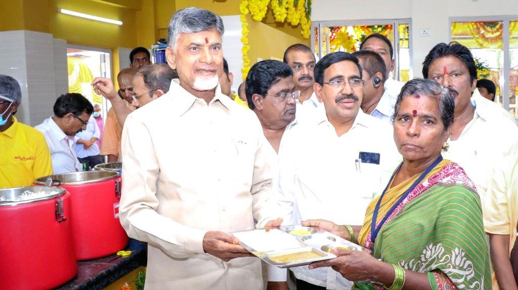 Andhra Pradesh Chief Minister N. Chandrababu Naidu serves food to a woman during the inauguration ofAnnapurna canteen, in Vijayawada on July 11, 2018. - N. Chandrababu Naidu