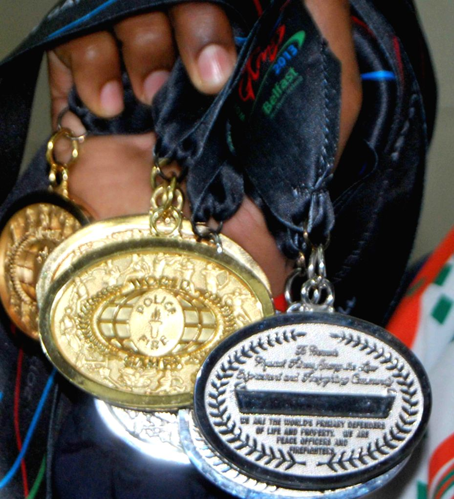 Andhra Pradesh Police swimmer Tulasi Chaitanya, a constable, with his medals during a press conference with ADG Sports Rajiv Trivedi in Hyderabad on August 16, 2013. Tulasi Chaitanya has bagged 3 ...