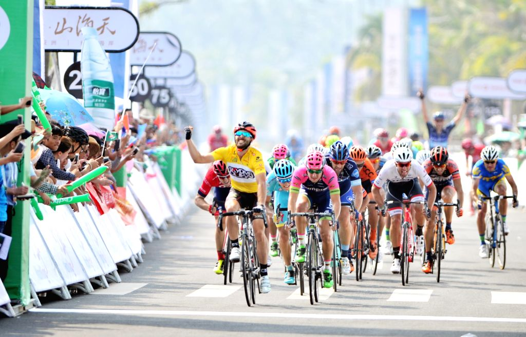 Andrea Palini (in yellow) celebrates before he crosses the finish line during the 2nd stage of the 2015 Tour of Hainan International Road Cycling Race in Wenchang, ...
