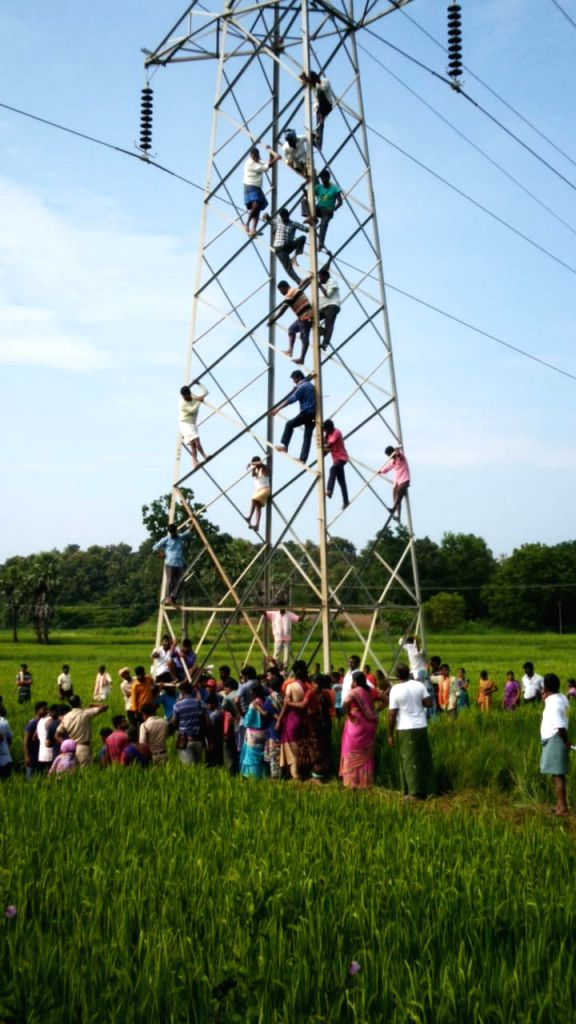 Angry farmers climb high voltage AC transmission tower to threaten the Government of committing mass suicide over the non-redressal of their grievances, at Kasturinagaram village of ...