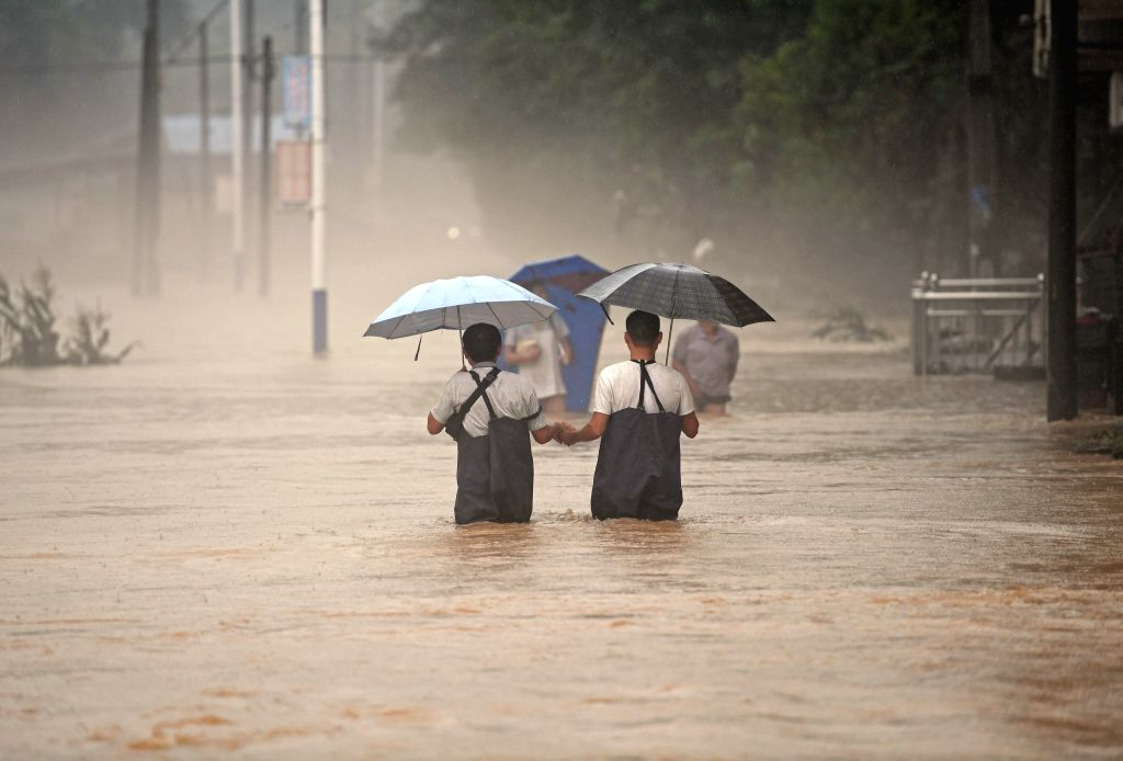 ANHUA, June 30, 2017 - People walk on a flooded street in Anhua County, central China's Hunan Province, June 30, 2017. Lasting heavy rainfall from June 22 has led to floods in many parts of Hunan.
